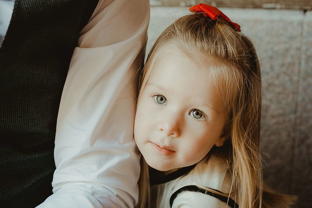 portrait of daughter with beatiful green eyes, blonde hair and red ribbon in hair looking into the camera while leaning against dad