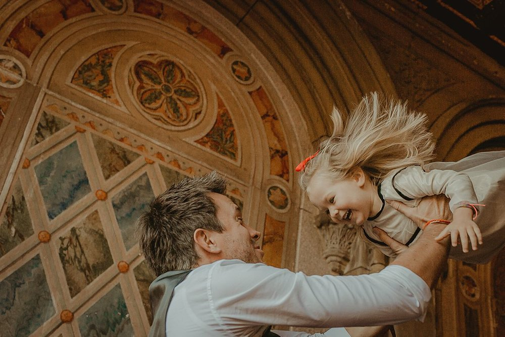candid photo of dad throwing daughter in the air at bethesda terrace in central park. image by nyc family photographer krystil mcdowall