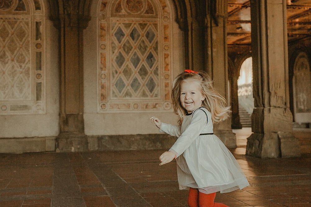 candid playful photo of young girl running around laughing at bethesda terrace in central park nyc. image by krystil mcdowall photography