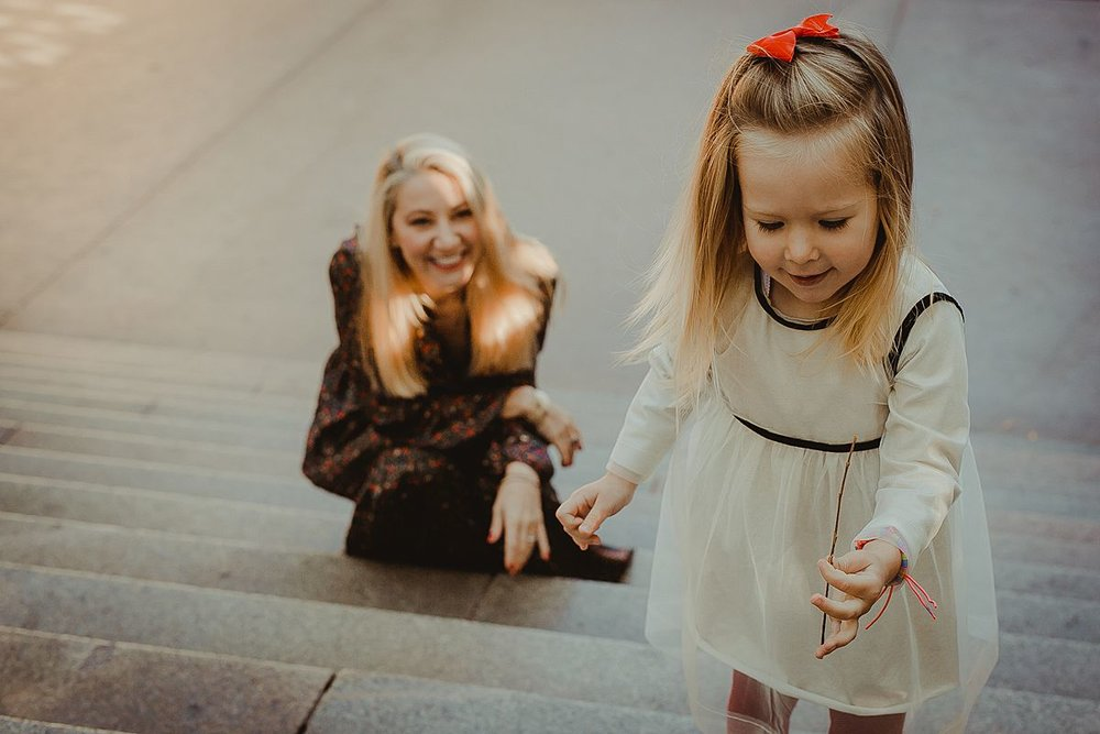 candid photo of daughter playing with sticks on stairs in central park's bethesda terrace. image by nyc family photographer krystil mcdowall