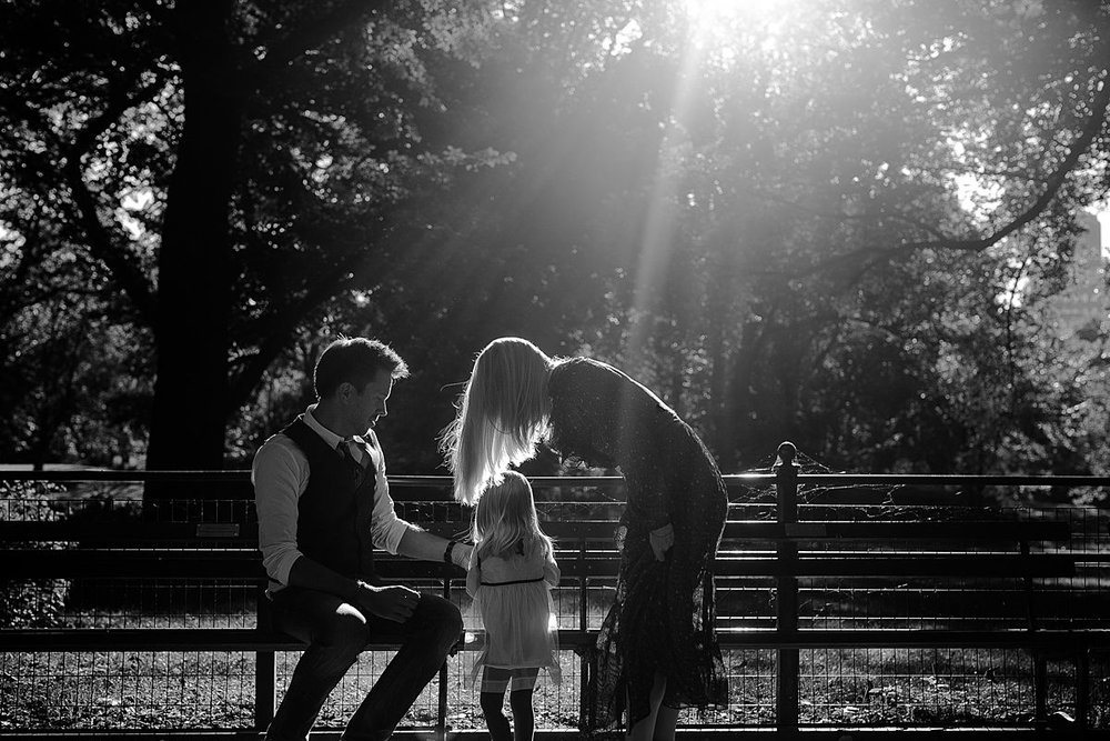 black and white candid image of mom, dad and daughter sitting on park bench during candid family photo session with krystil mcdowall photography