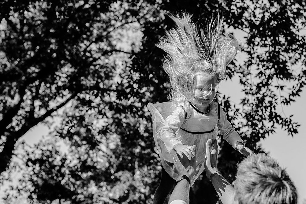dad throws daughter in the air in candid family photo session with krystil mcdowall photography
