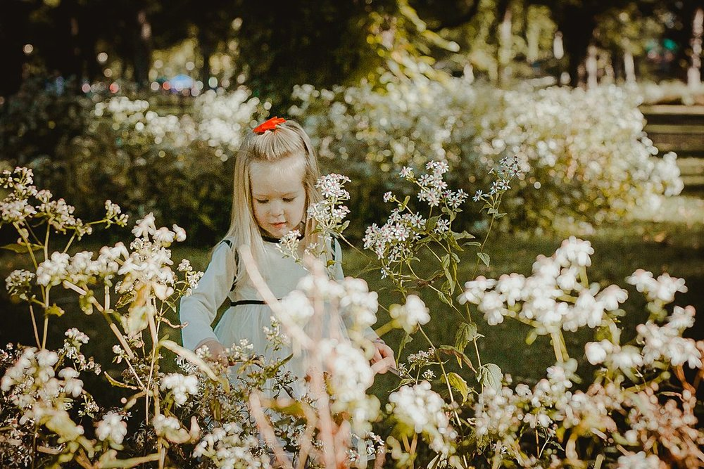 young girl playing amongst white flowers in central park new york city