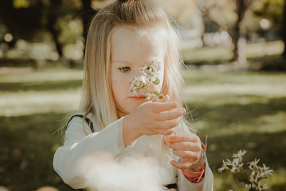 girl holds beautiful white flowers in central park nyc. photo by nyc family photographer krystil mcdowall