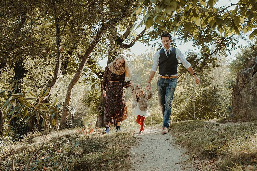 candid family photo as family walks though trails in central park. image by nyc family photographer krystil mcdowall