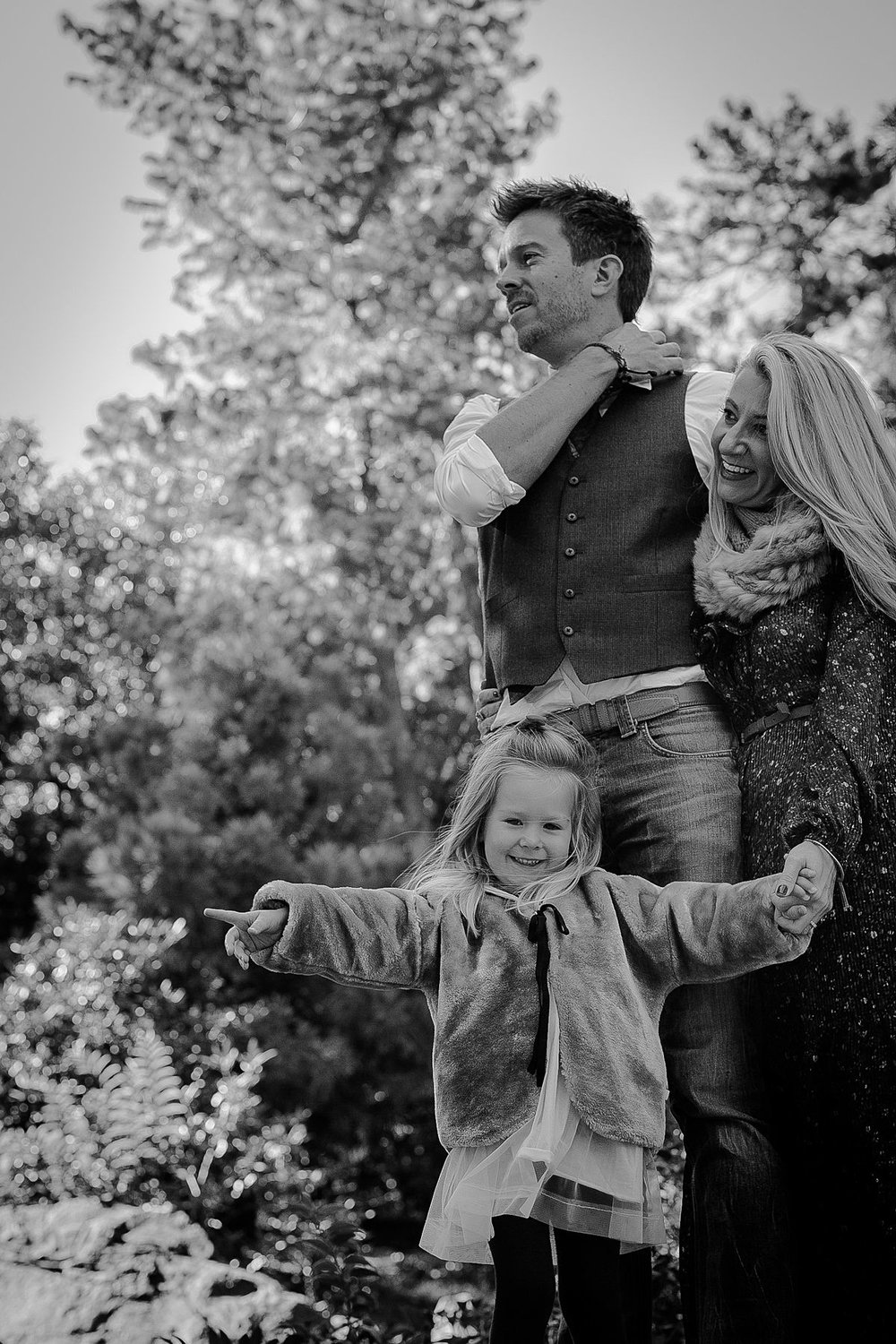black and white candid family photo as family walks though trails in central park. image by nyc family photographer krystil mcdowall