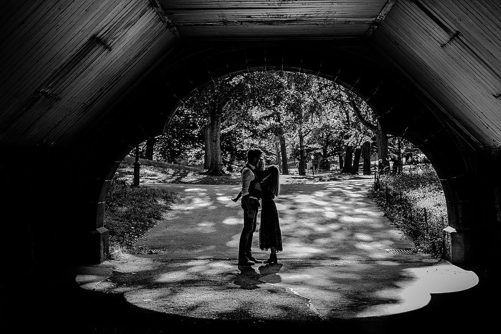 silhouette image mom, dad and toddler under bridge in central park. image by nyc family photographer krystil mcdowall