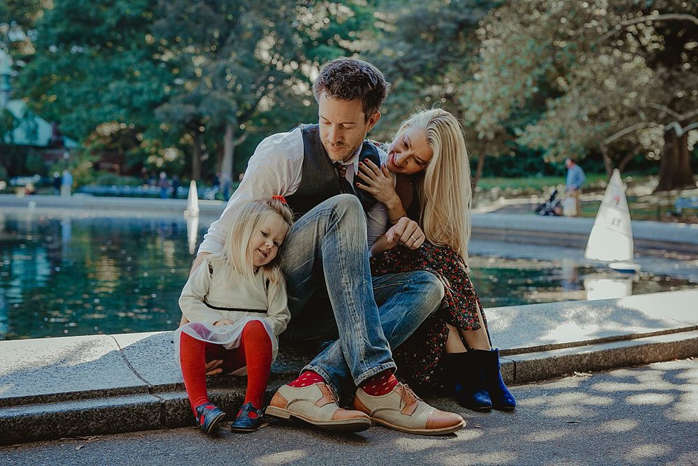 family portrait of mom, dad and daughter sitting in central park during documentary family photo session in nyc