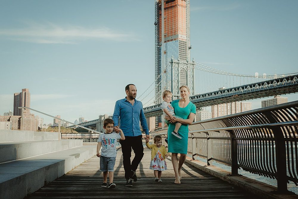 candid photo of family of five walking along the brooklyn promenade. photo by nyc family photographer krystil mcdowall