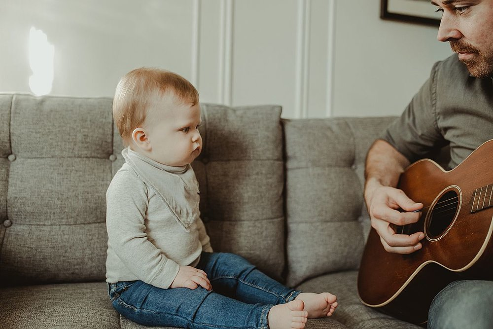 dad plays guitar while son watches curiously. capturing candid family moments to be treasured for a lifetime. krystil mcdowall photography