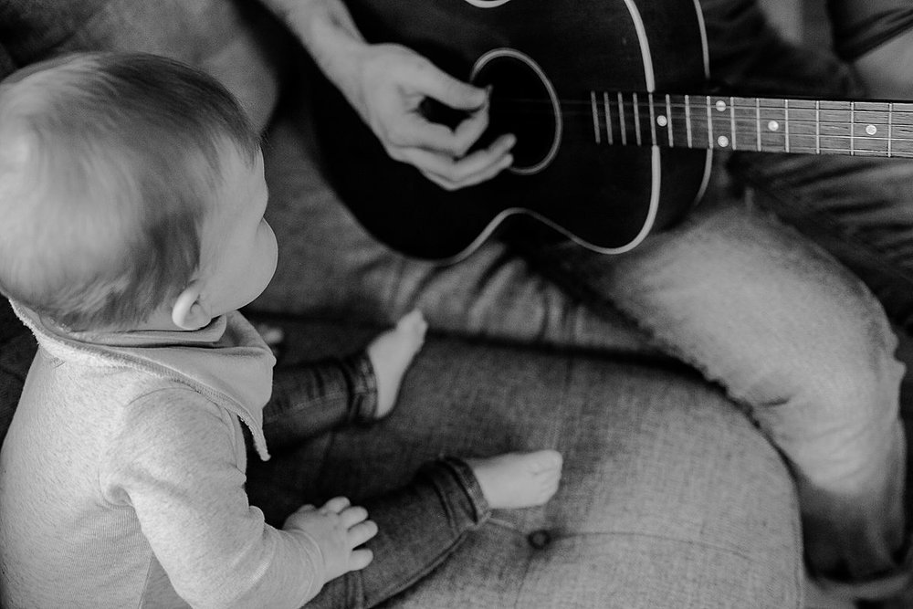 black and white image of dad sitting on couch and playing guitar for his son. dad and son sitting on living room couch while dad plays guitar for his eight month old son during fun family photo session. image by nyc family photographer krystil mcdowall