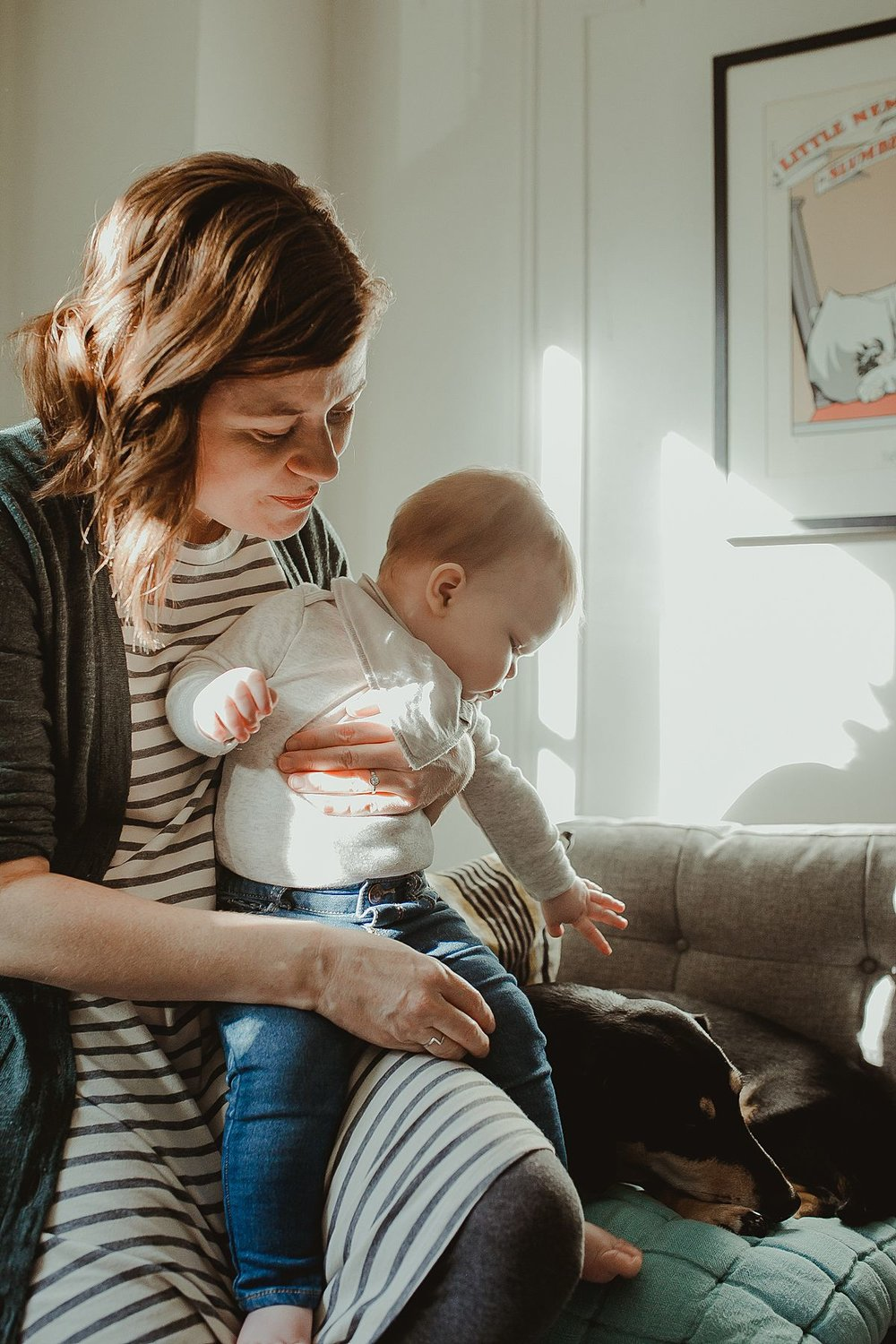 mom, baby and dog on sun filled living room during documentary family photo session. image by nyc family photographer krystil mcdowall