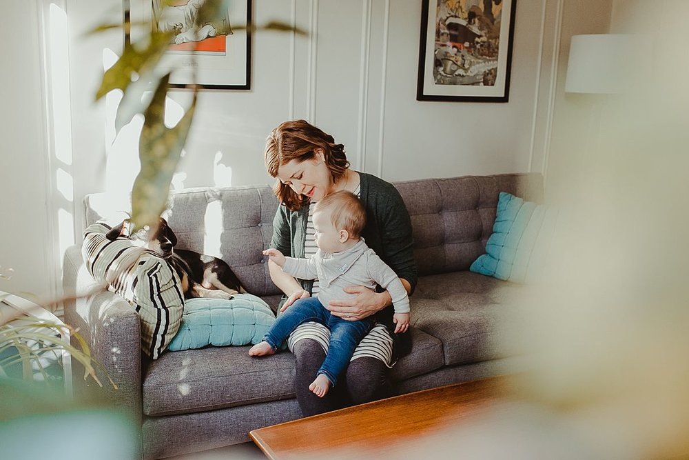 peeking at mom, baby and dog through plants in the living room during nyc family photo session. image by krystil mcdowall photography