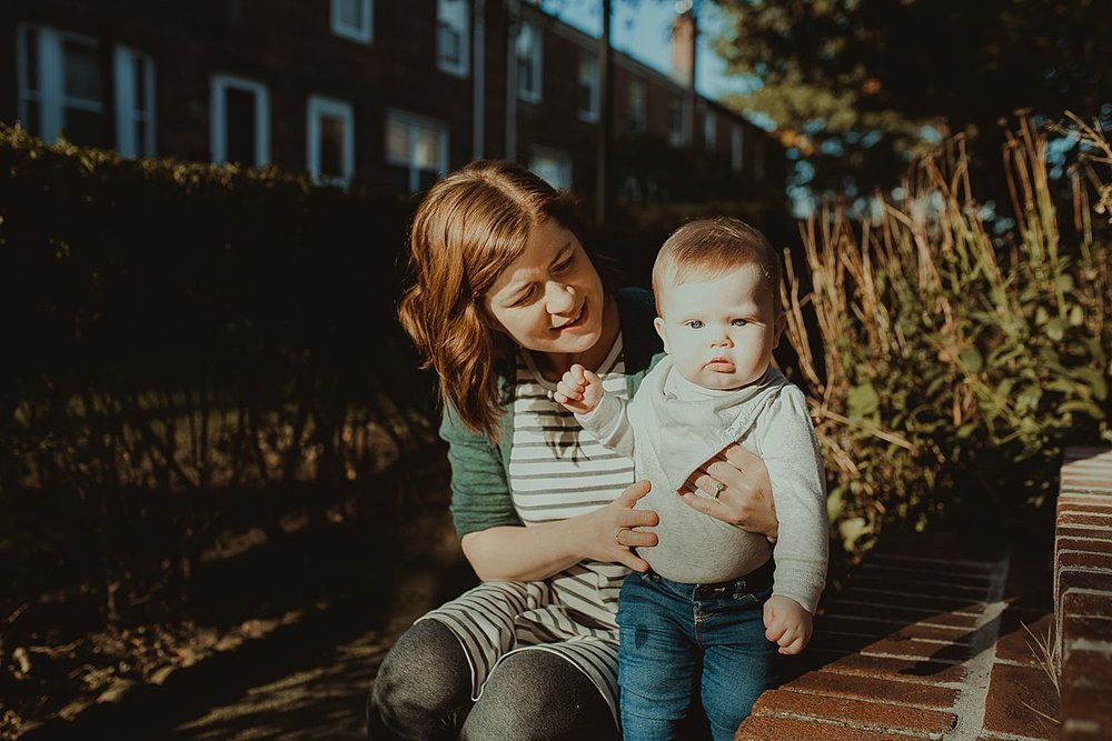 mom and son sitting enjoying the morning sun while sitting on apartment stairs during nyc family photo session. image by nyc family photographer krystil mcdowall