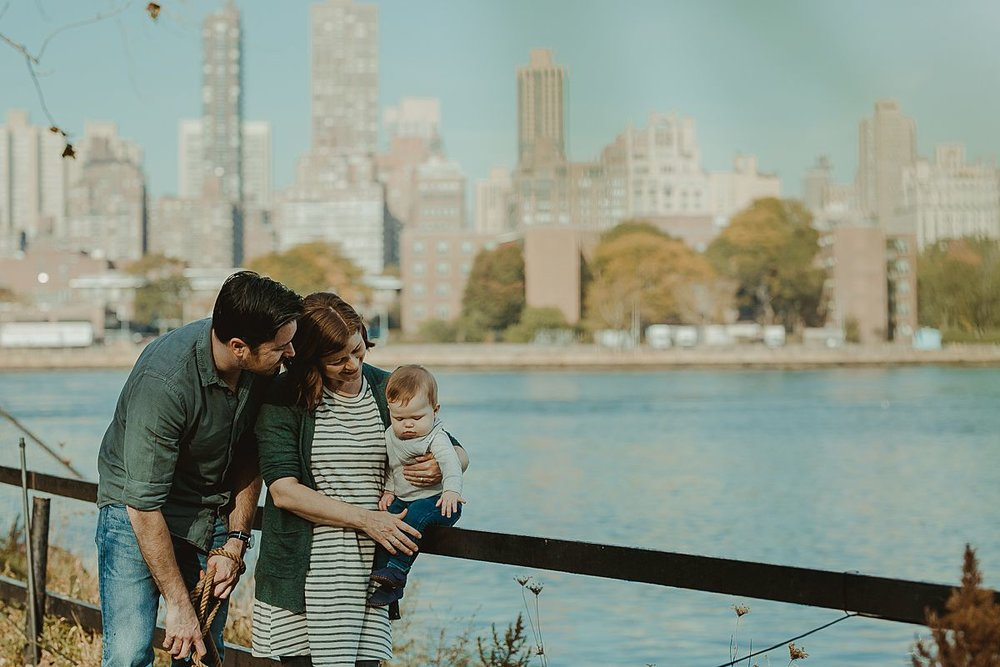 family portrait at socrates sculpture park with manhattan skyline in the background. image by nyc family and newborn photographer krystil mcdowall