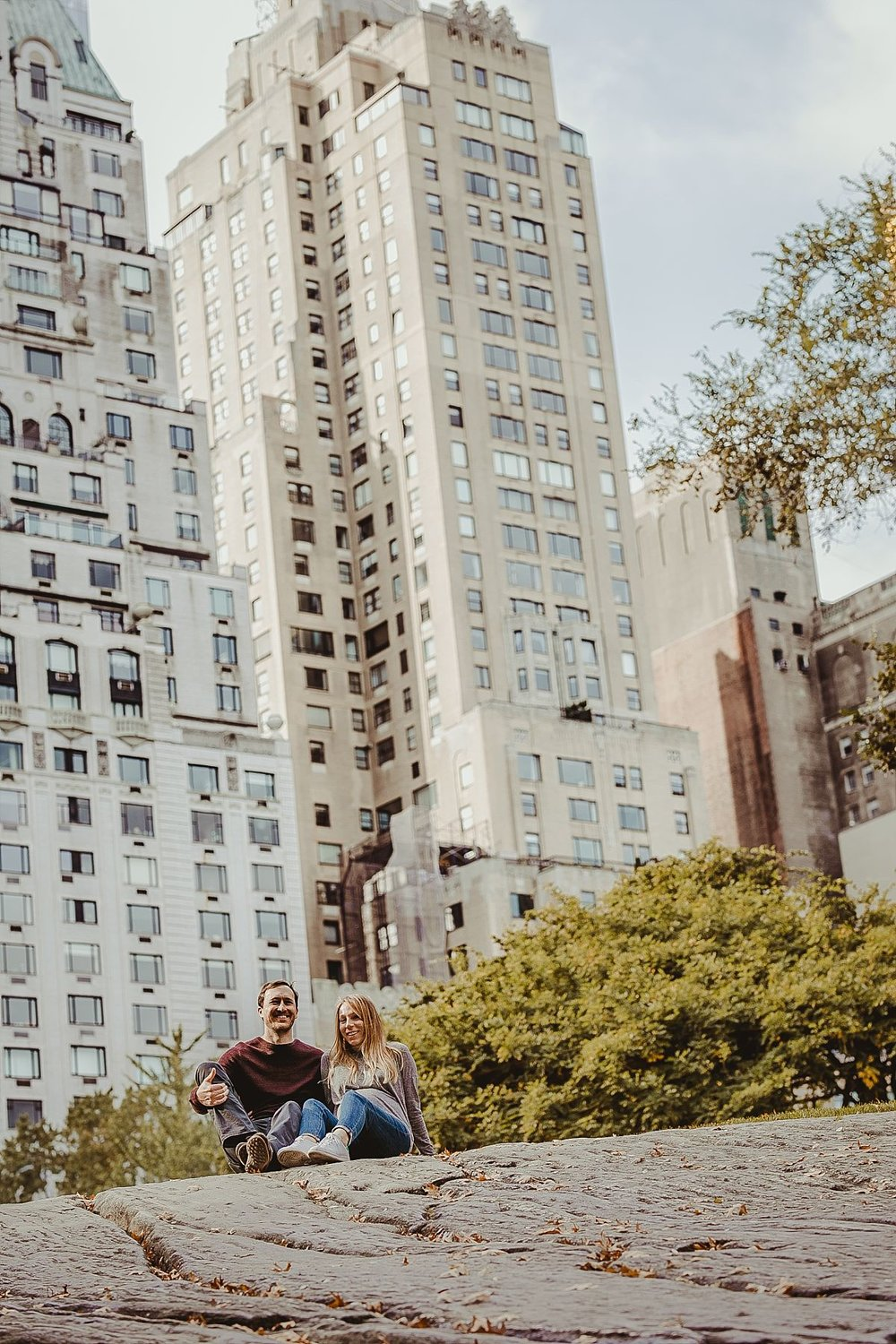 couple sitting on rock in central park in front of essex building on beautiful fall day. photographed by nyc family and newborn photograher krystil mcdowall