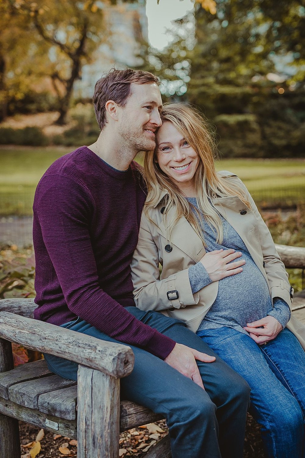 expecting couple sitting in in front of pond on sunny morning in central park nyc. photographed by nyc maternity photograher krystil mcdowall