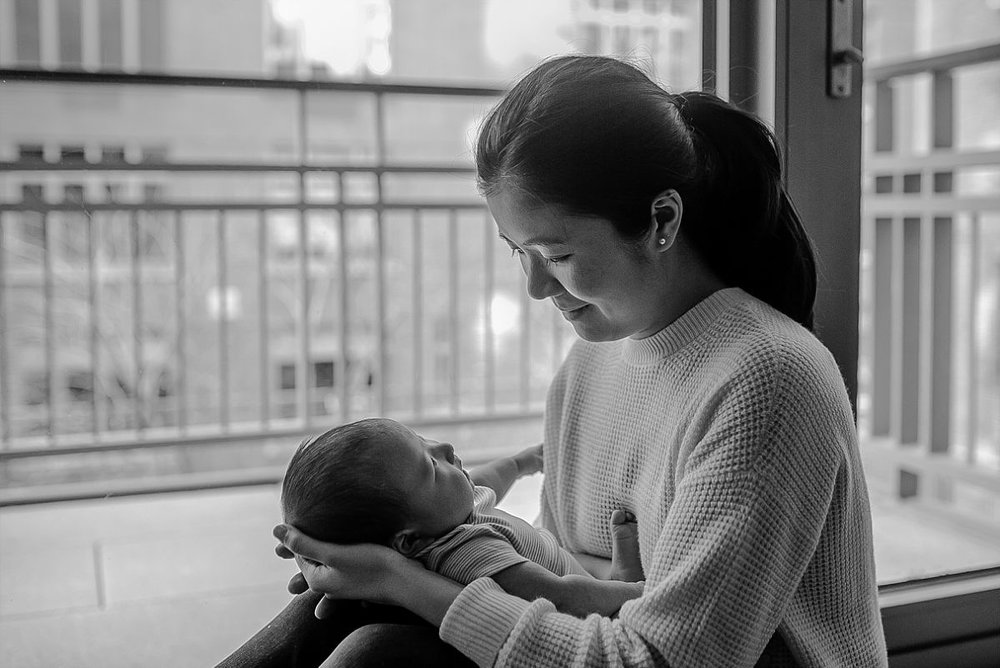 black and white portrait of mom holding newborn son sitting against window of nyc apartment
