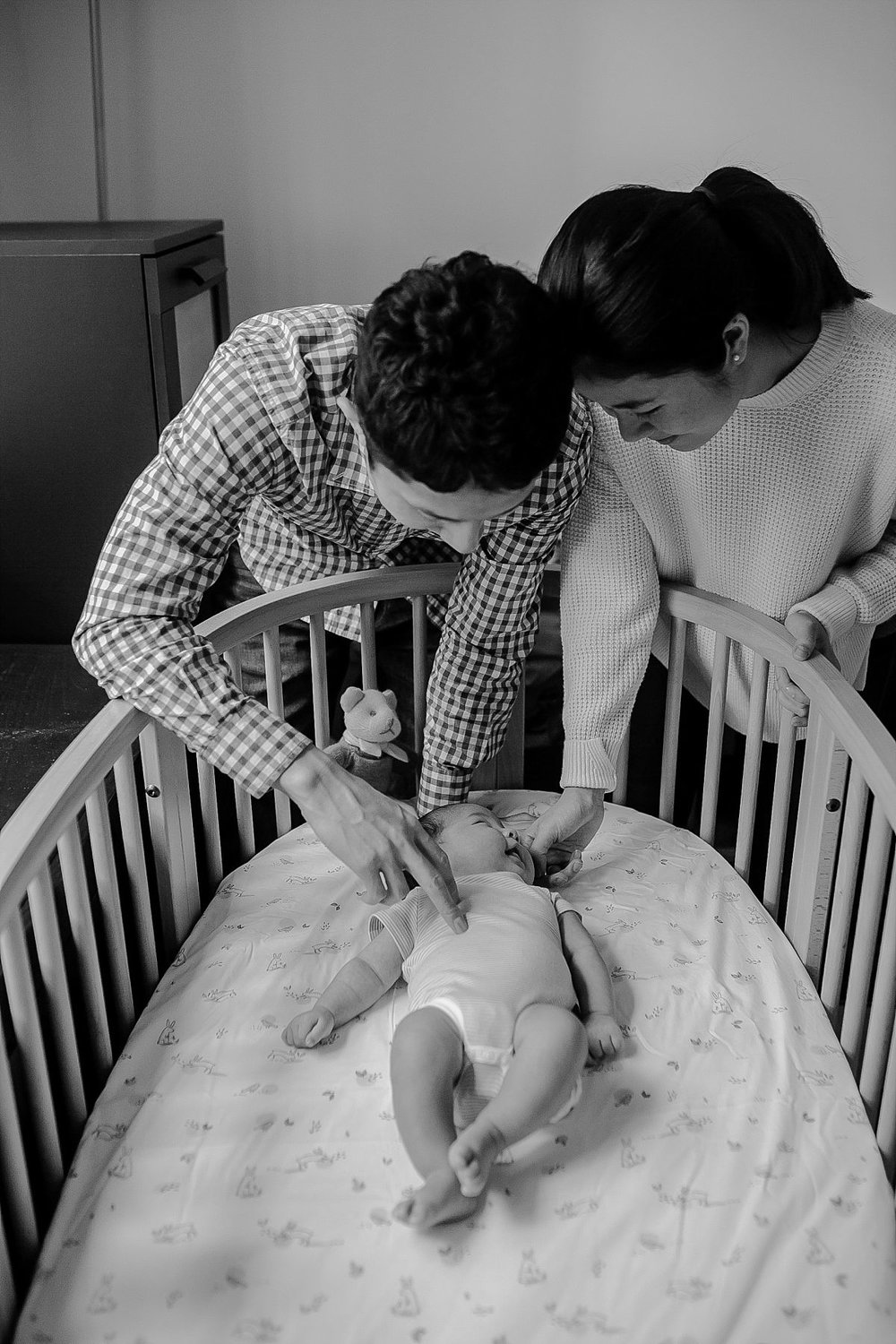 photo of mom and dad playing with newborn son as he lays in his crib. photo by nyc newborn photographer krystil mcdowall