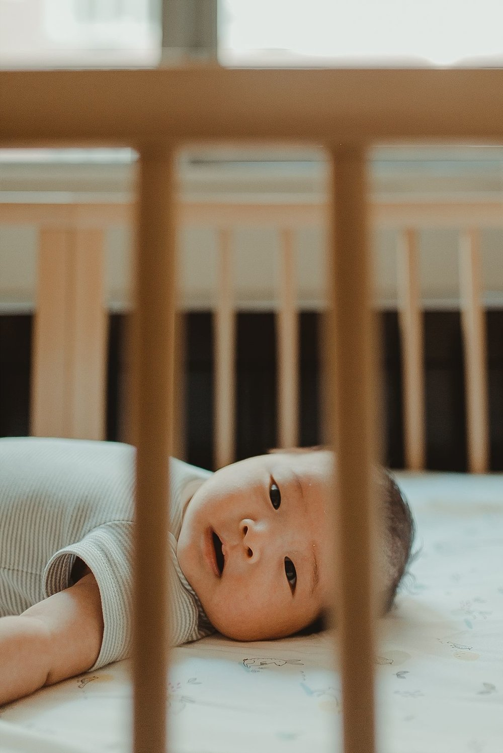 portrait of as he looks at camera through crib rails. photo by nyc newborn photographer krystil mcdowall