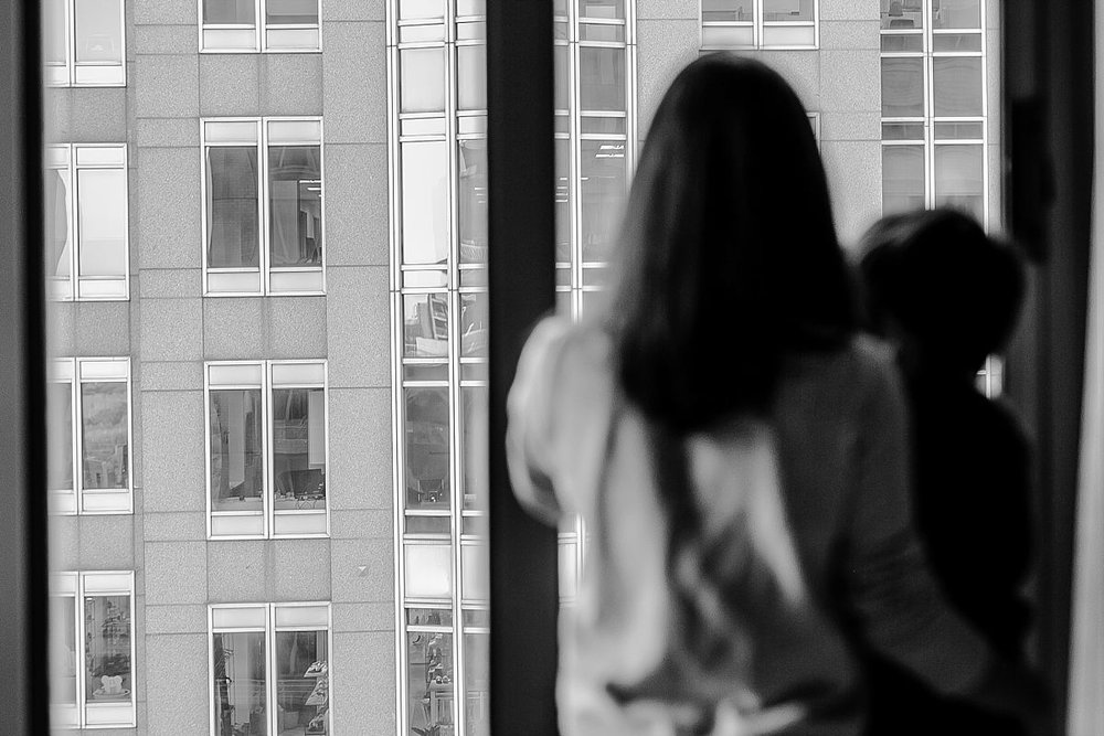 blurred portrait of mom and son looking out at manhattan buildings from their nyc hotel room. photo taken by krystil mcdowall photography