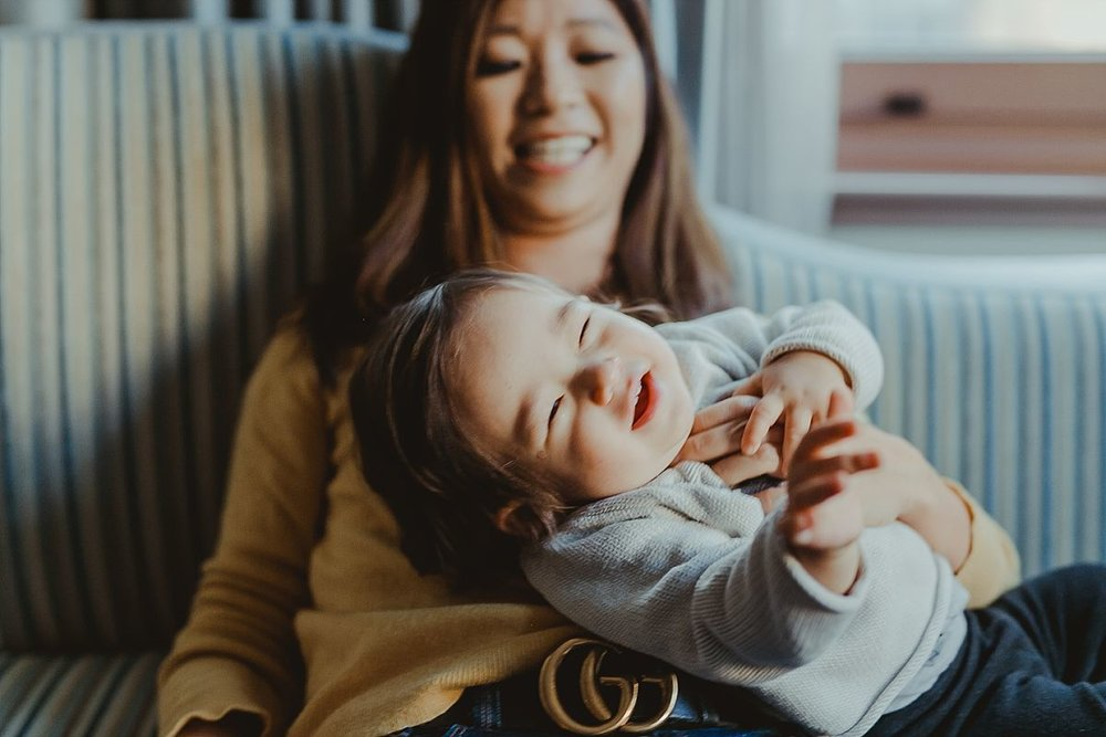 mom tickling daughter and laughing together on hotel sofa lounge during candid family photo shoot in manhattan. image by krystil mcdowall