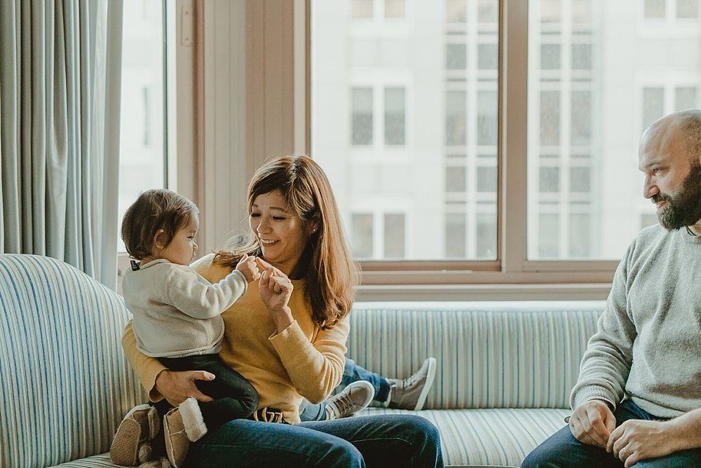 candid image of dad looking at mom and daughter as they play and laugh together. image by nyc family photographer krystil mcdowall