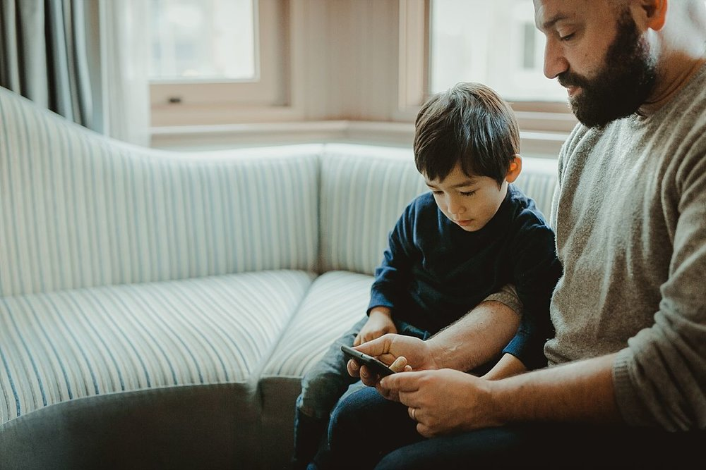 dad and son playing iphone games on hotel sofa bed during vacation to new york city. photo by photographer krystil mcdowall