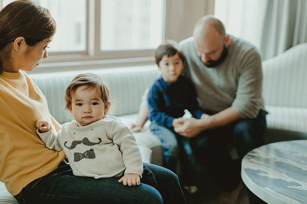 photo of dad, son, mom and daughter on hotel sofa lounge of their midtown manhattan apartment. image taken by nyc family photographer krystil mcdowall