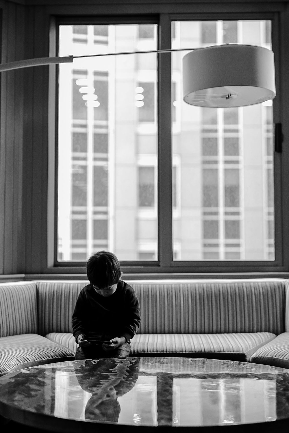 son playing iphone while waiting for mom and daughter to get ready to go outside. image taken by nyc family photographer krystil mcdowall