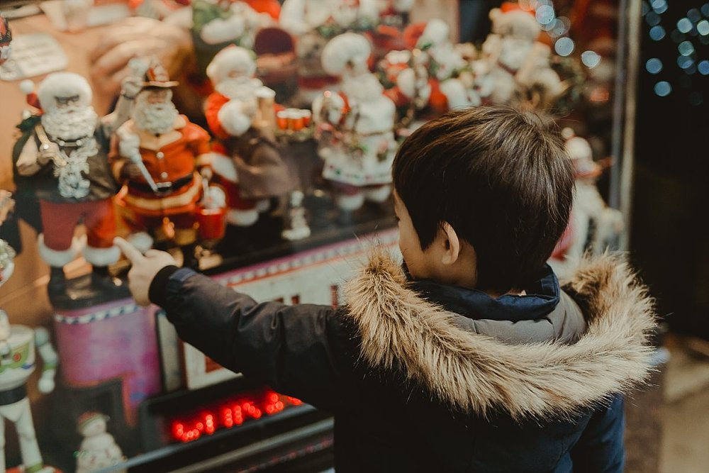 boy points at santa statues on the streets of midtown manhattan during candid family photo session in nyc. image by nyc family photographer krystil mcdowall