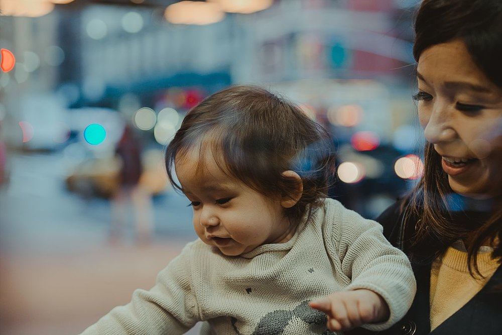 mom and daughter look at christmas ornaments on the streets of midtown manhattan during candid family photo session in nyc. image by nyc family photographer krystil mcdowall