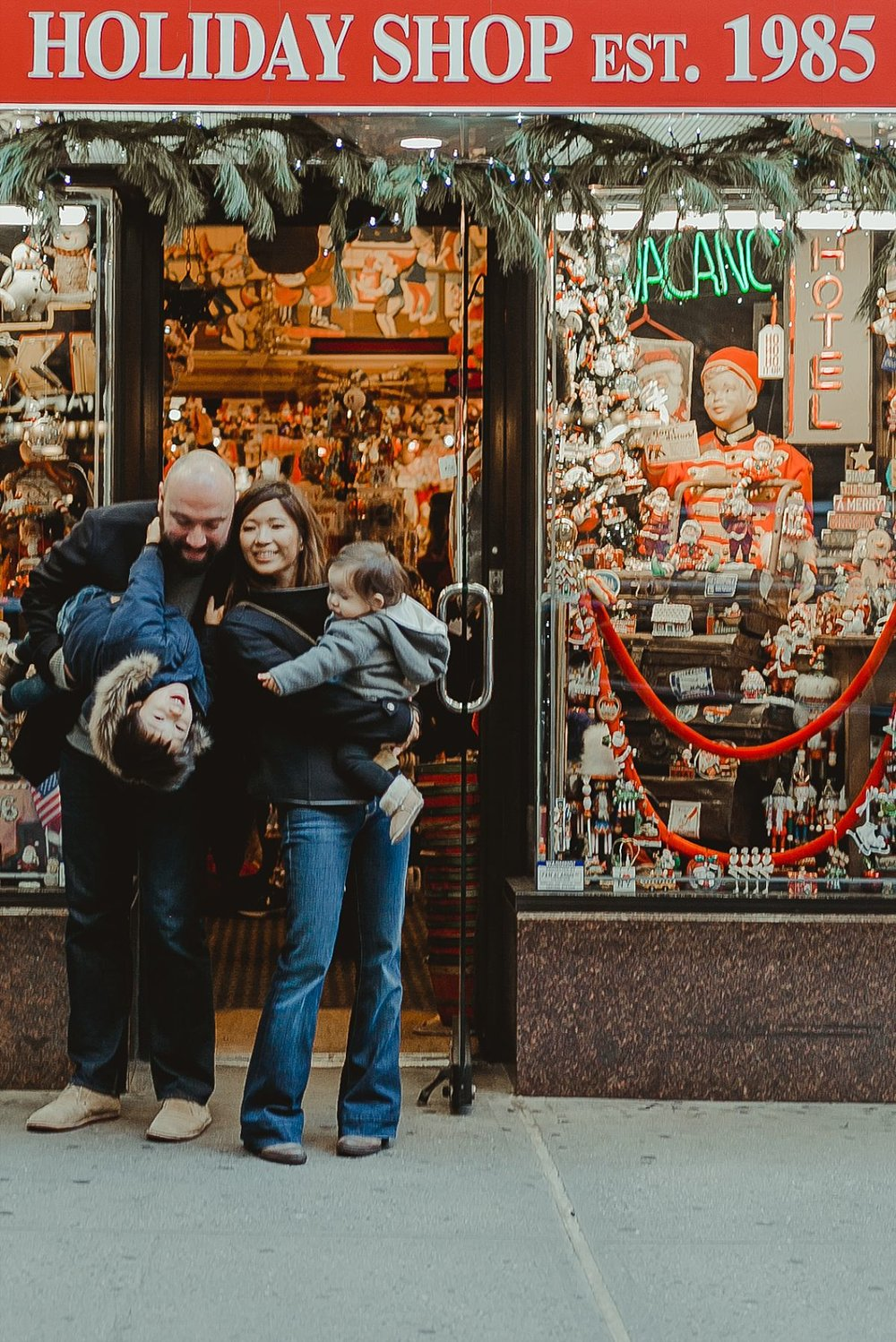 candid family portrait out front of christmas shop in midtown manhattan. image by nyc family photographer krystil mcdowall