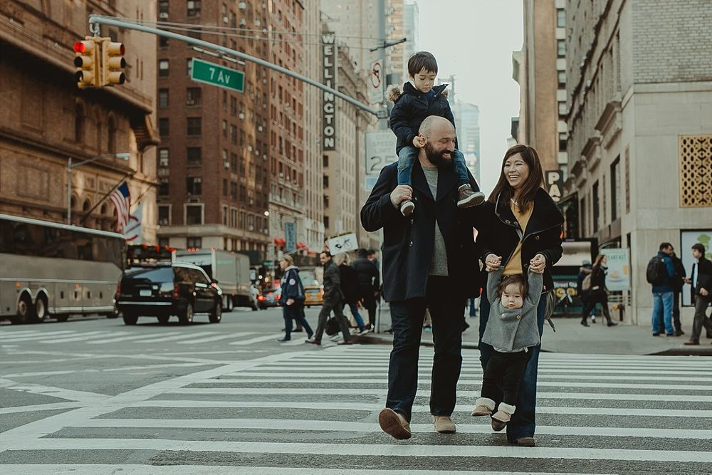 family of four walking the streets of midtown and laughing while they do so. image taken by photographer krystil mcdowall