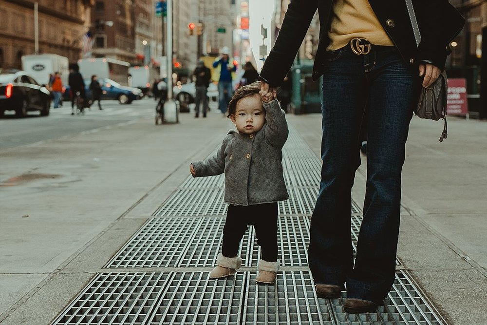mom and daughter walking the streets of midtown manhattan during documentary family photo session. image by nyc family photographer krystil mcdowall