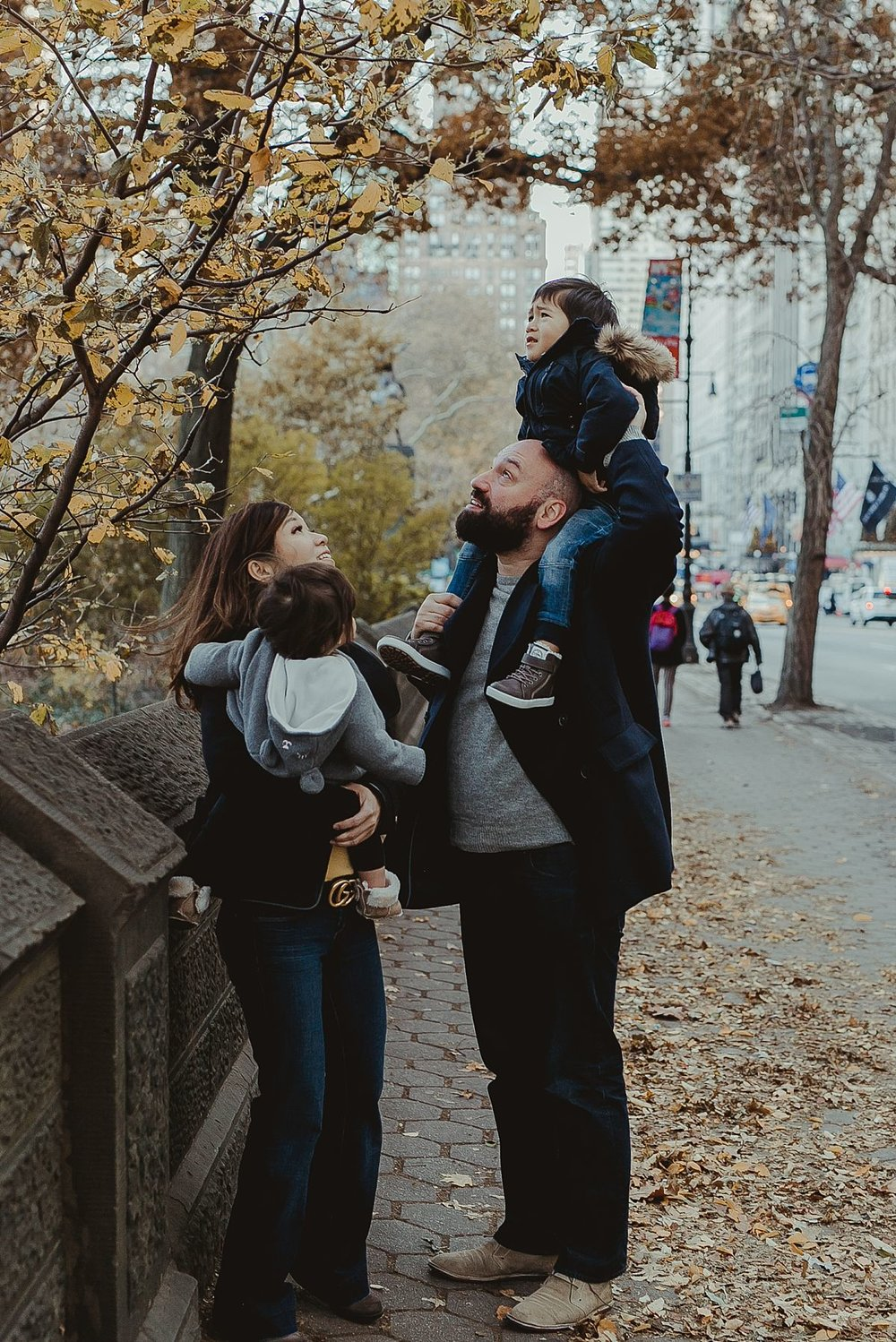family playing with leaves of tree at the bottom of central park on chilly winters day. photo by nyc family photographer krystil mcdowall