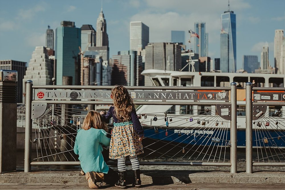candid photo of young girls as they explore the lockets at pier in dumbo brooklyn. photo by nyc family photographer krystil mcdowall