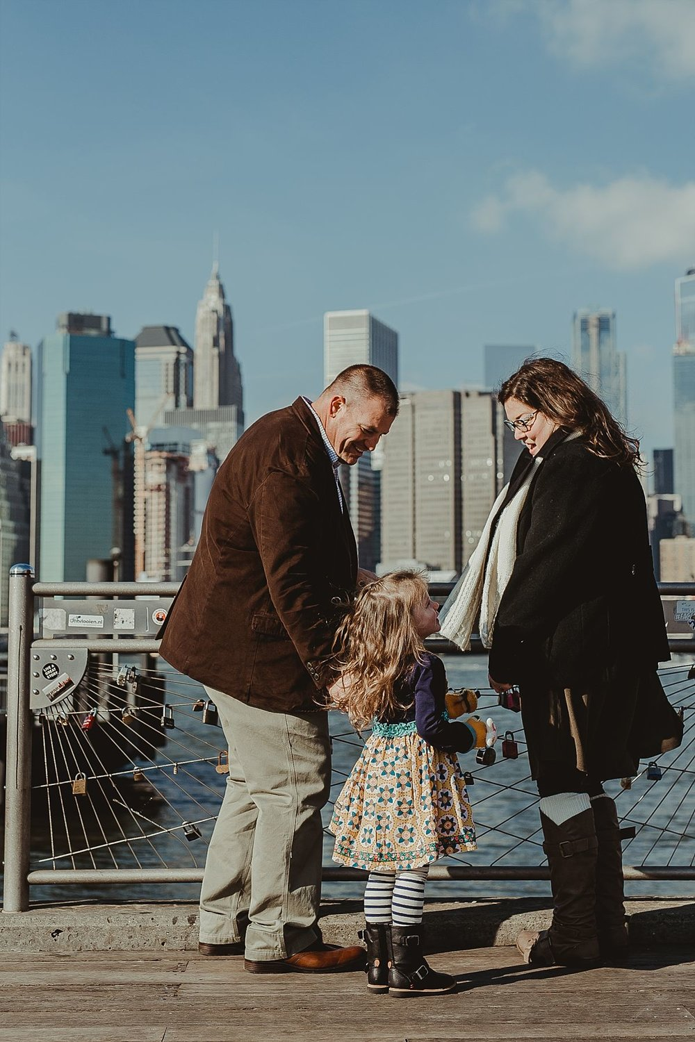 mom, dad and daughter at dumbo pier looking at the nyc skyline and the lockets. photo by krystil mcdowall photography