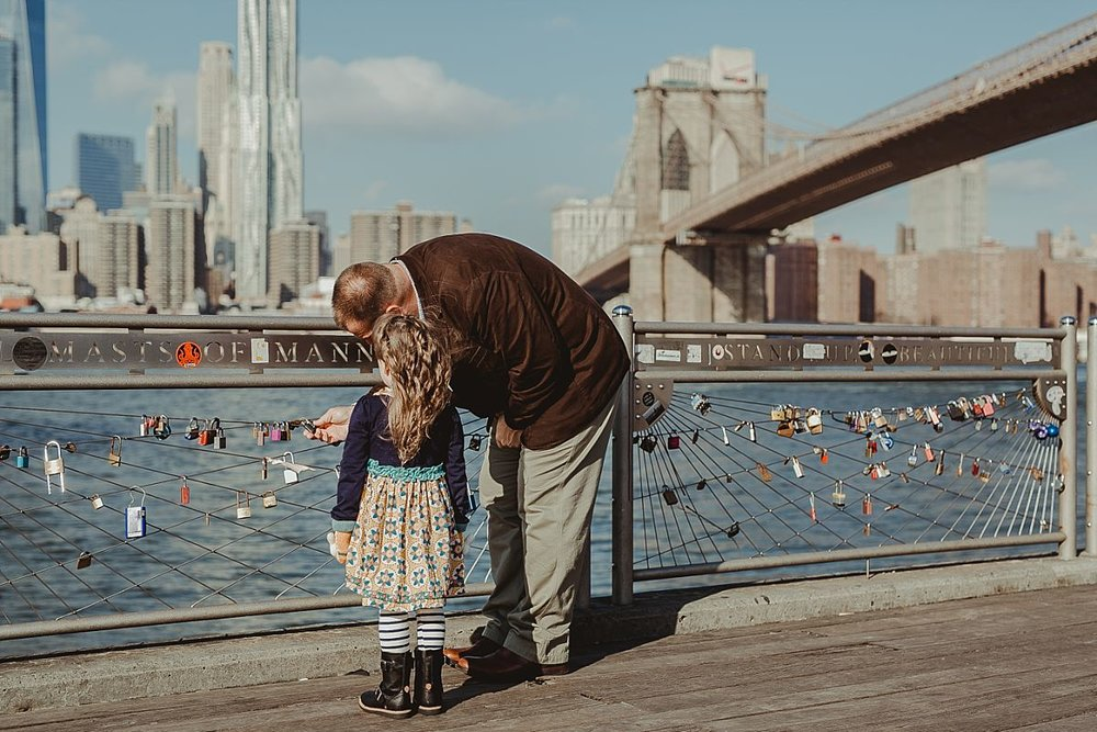 candid dad and daughter portrait as they explore the lockets at pier in dumbo brooklyn with the brooklyn bridge in the background. photo by nyc family photographer krystil mcdowall