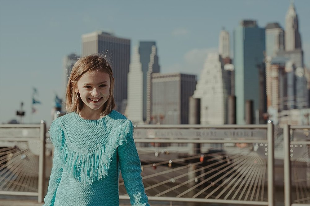 portrait of girl in bright blue sweater playing on the pier with the nyc skyline in the background. photo by nyc family photographer krystil mcdowall