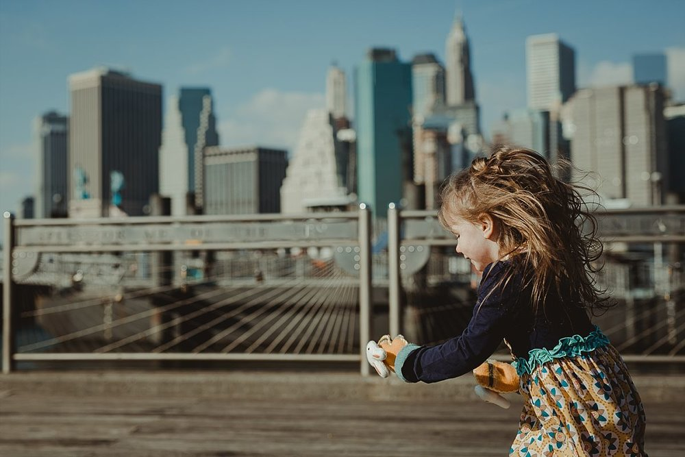 portrait of girl in navy blue dress at the pier at dumbo with the nyc skyline in the background. photo by nyc family photographer krystil mcdowall