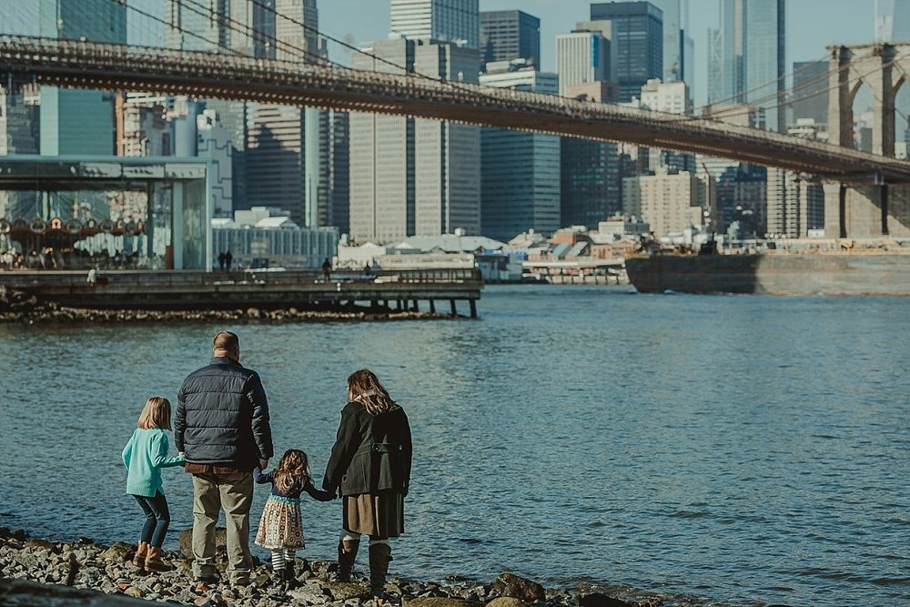 family of four at brooklyn beach holding hands as they look out at the nyc skyline. documenting real memories for your family is krystil mcdowall photography