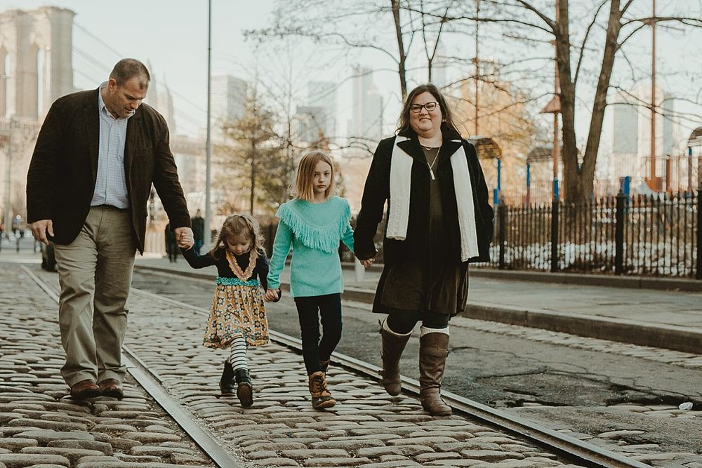 family of four walking along cobble stoned streets in brooklyn with the brooklyn bridge in the background. documenting real memories for your family is krystil mcdowall photography