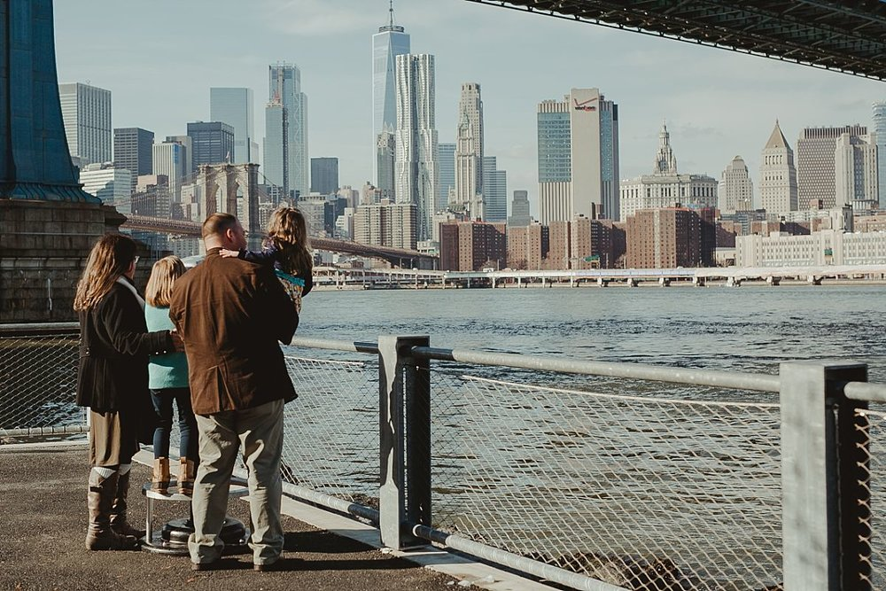 family looks out at the manhattan skyline while standing in front of the manhattan bridge. image by nyc family photographer krystil mcdowall