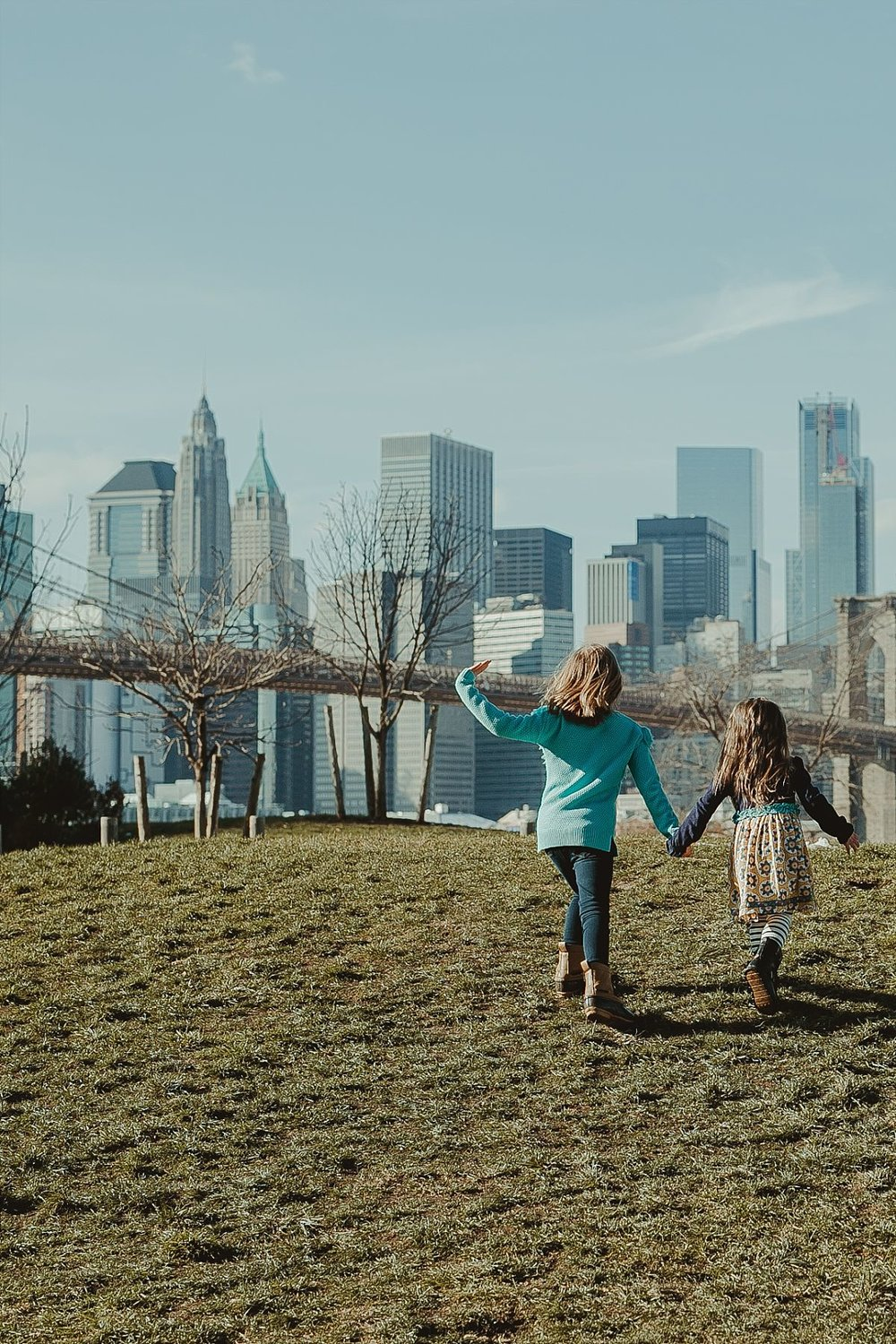sisters run hand-in-hand along the green grass in playground in brooklyn with beautiful views of the nyc skyline in the background. image by krystil mcdowall photography