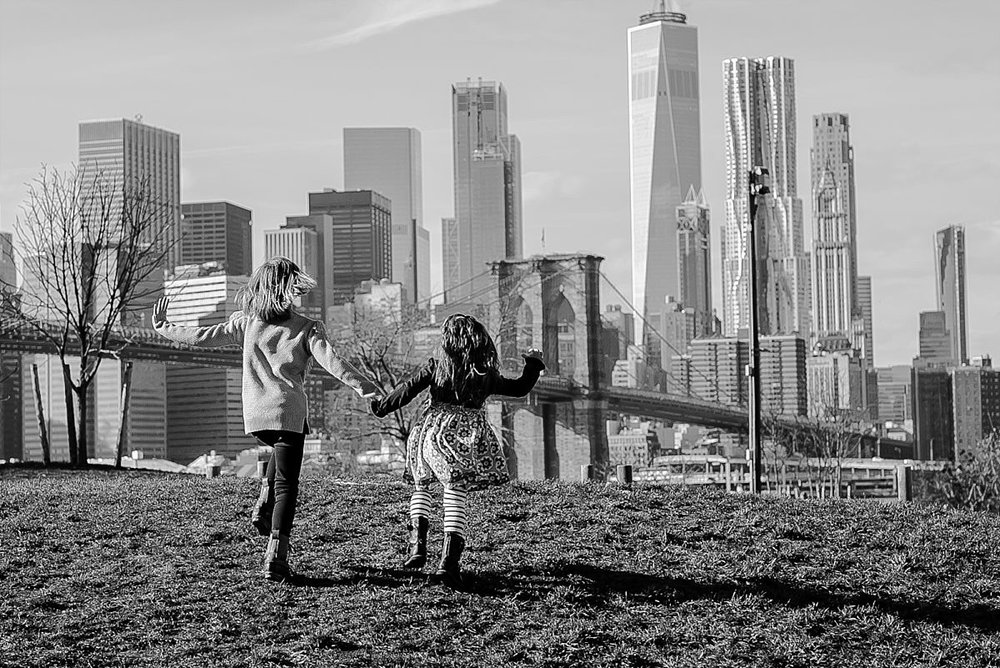 candid images of sisters running hand-in-hand along the grass in playground in brooklyn with beautiful views of the nyc skyline in the background. image by krystil mcdowall photography