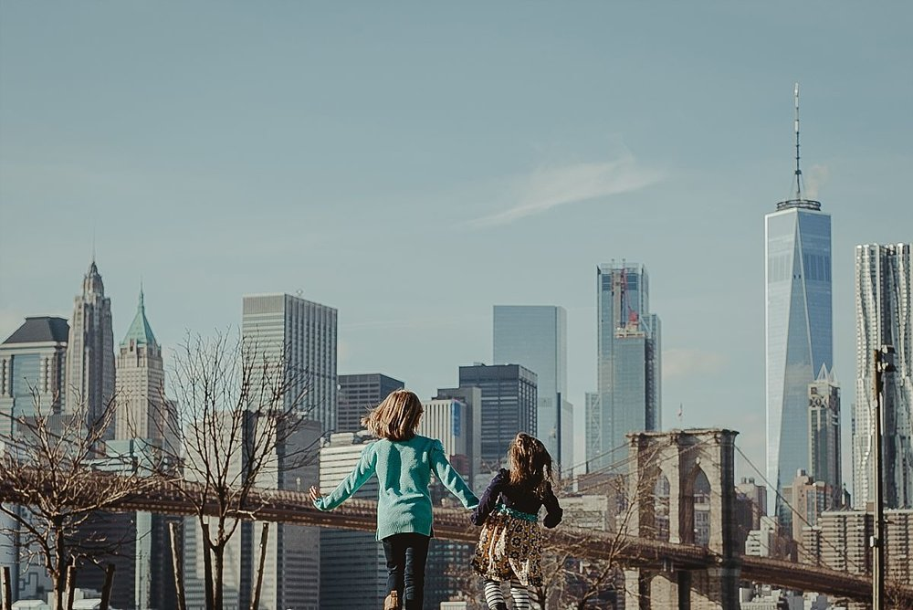 sisters run hand-in-hand in brooklyn with beautiful views of the nyc skyline in the background. image by nyc family photographer krystil mcdowall
