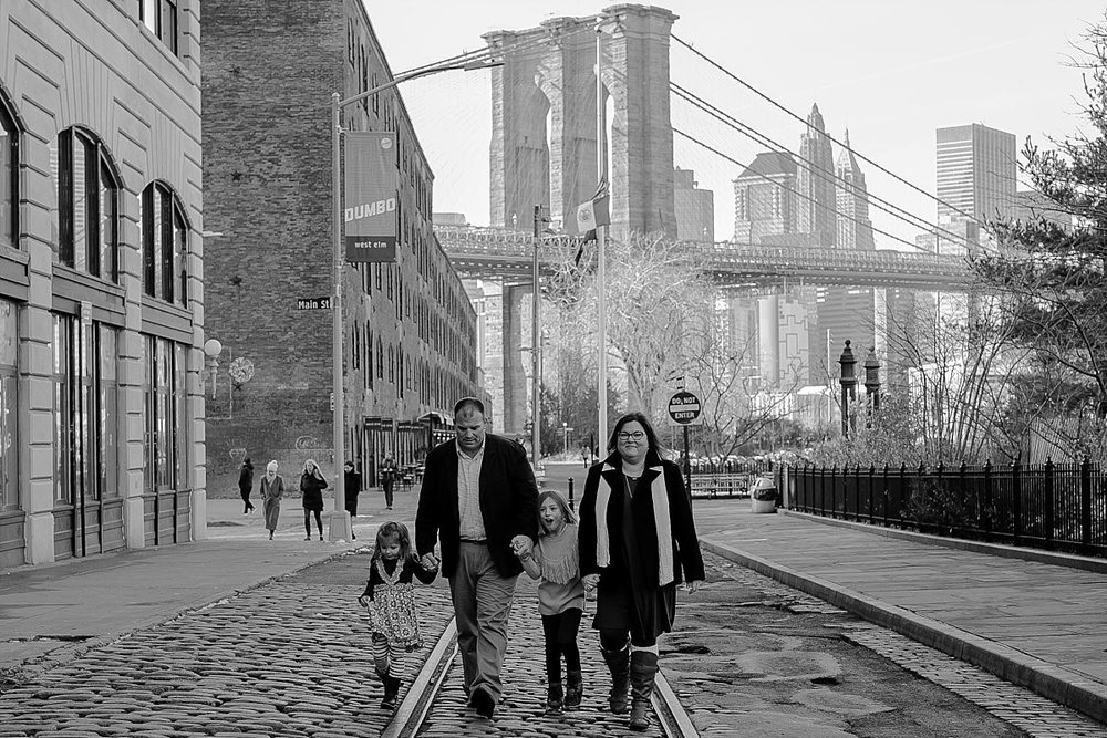 black and white photo of family waling along cobble stoned street in dumbo brooklyn with brooklyn bridge in the background