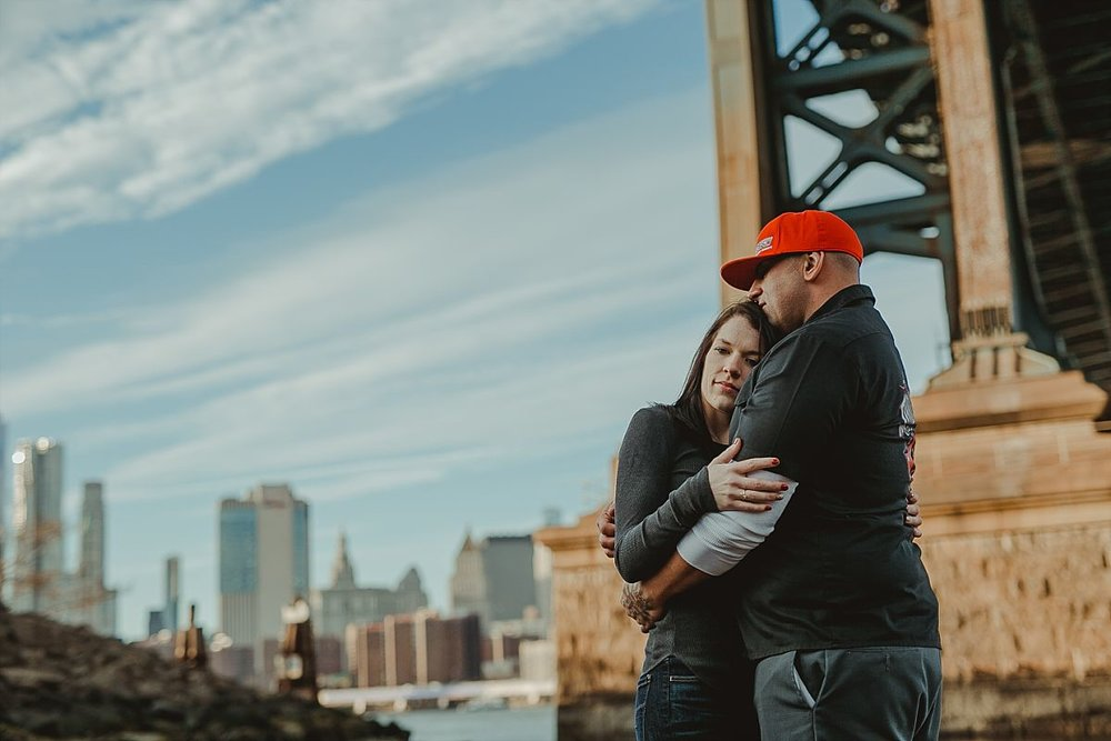 photo of couple hugging underneath manhattan bride in dumbo brooklyn during couples photoshoot. krystil mcdowall photography takes candid family photos