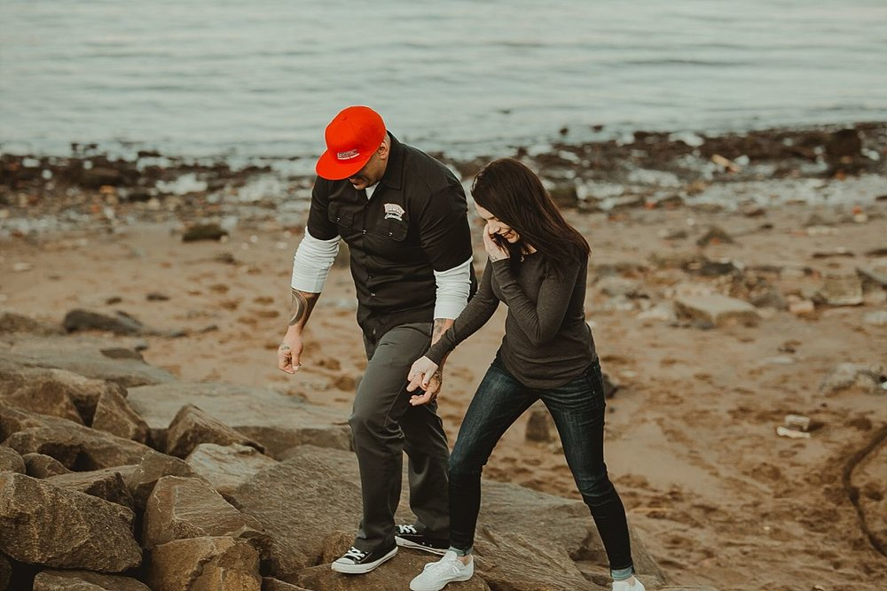 candid photo of couple walking on rocks underneath the manhattan bridge in dumbo brooklyn. photo of couple hugging underneath manhattan bride in dumbo brooklyn during couples photoshoot. krystil mcdowall photography takes candid family photos